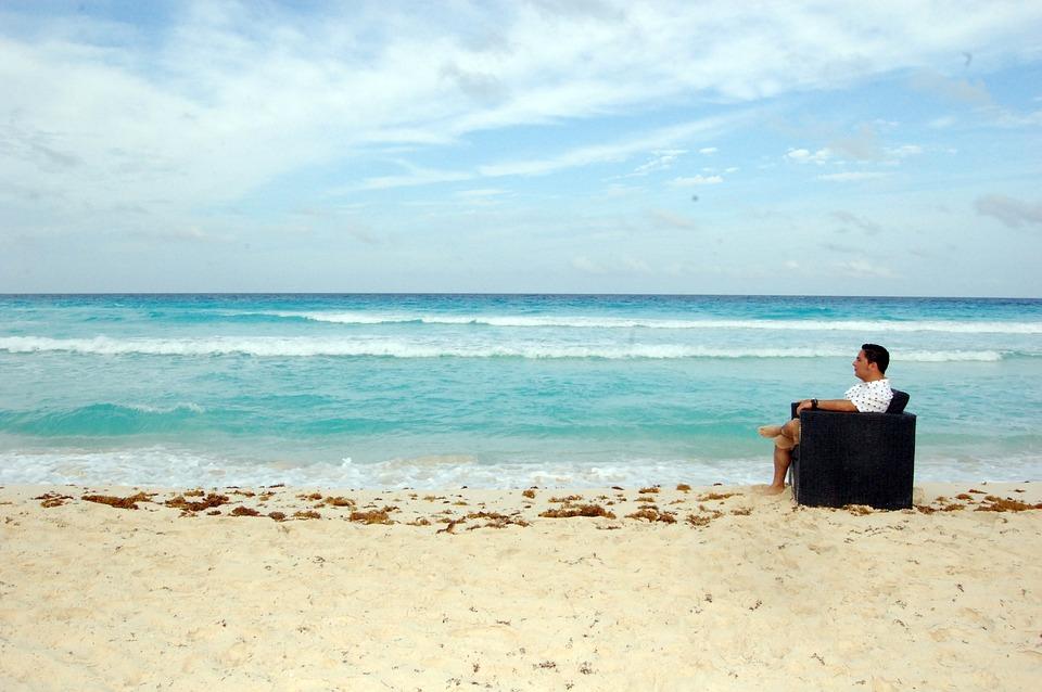 Foto hombre sentado en playa